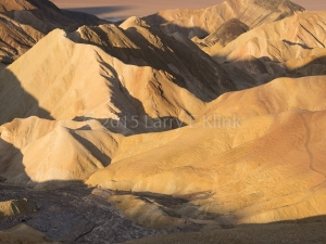A sculptural landscape of muted earth tones with water standing in both the erosion channels and in the valley below. Zabriske Point, Death Valley, CA OCT 2015.