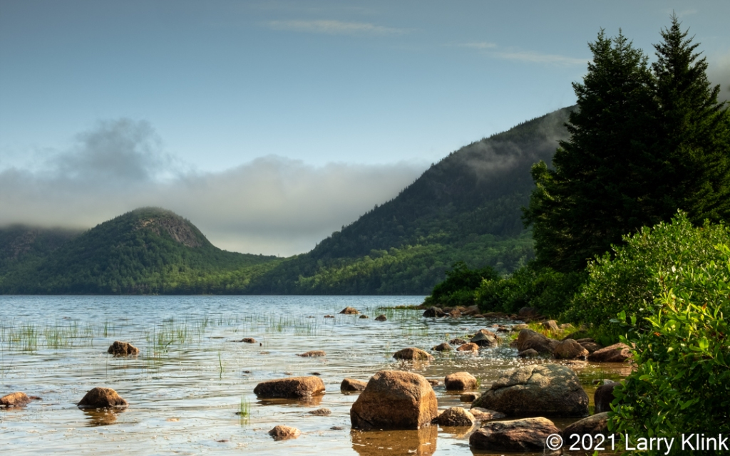 Photograph of sunrise over Jordan Pond at Acadia National Park. Includes pond, forest, and rocks.